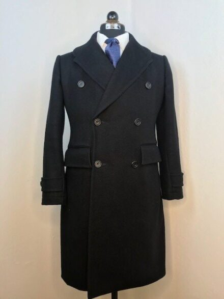 Double breasted top coat with french interlining in black heavy wool.